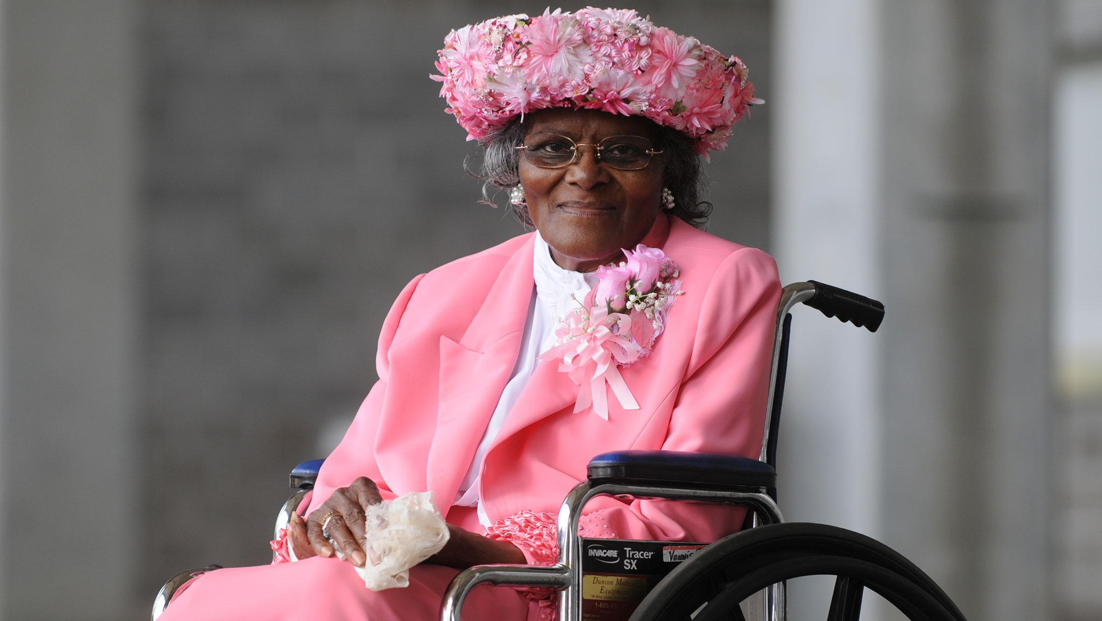 Woman in wheelchair with a feathered hat