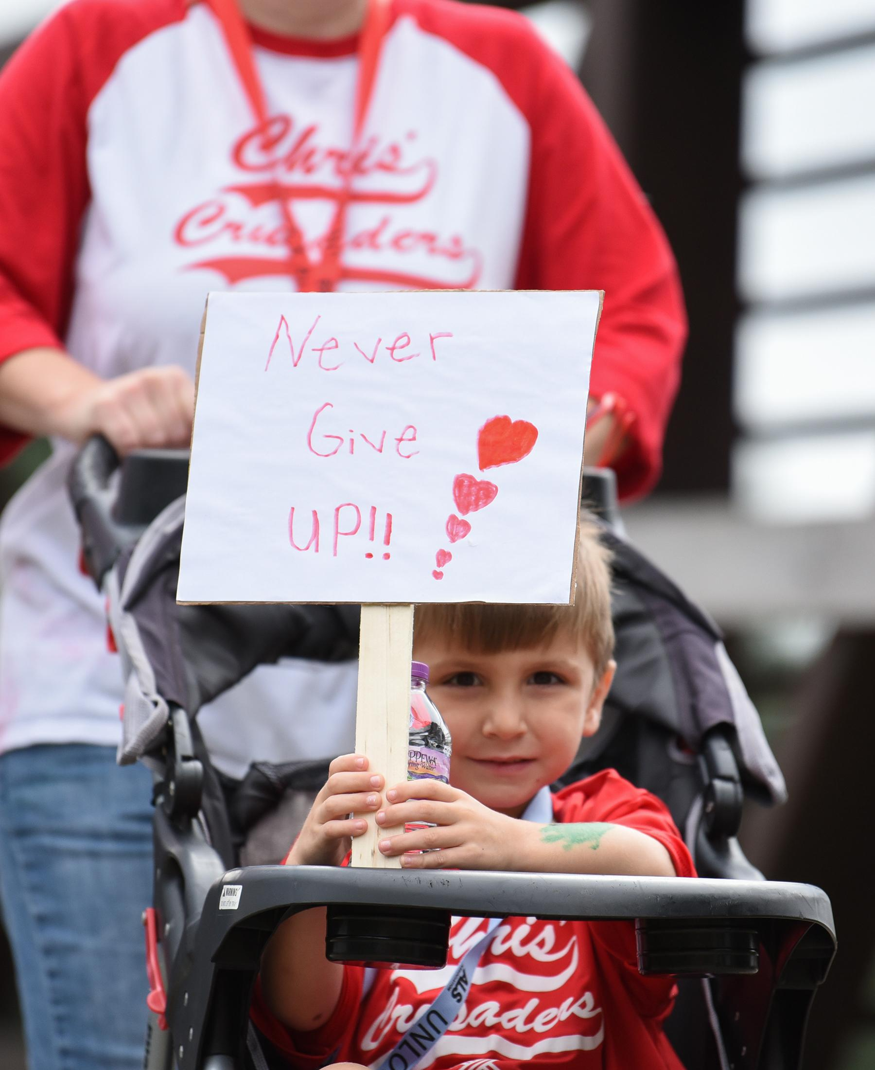 Child with a Never Give Up sign at a Walk to Defeat event