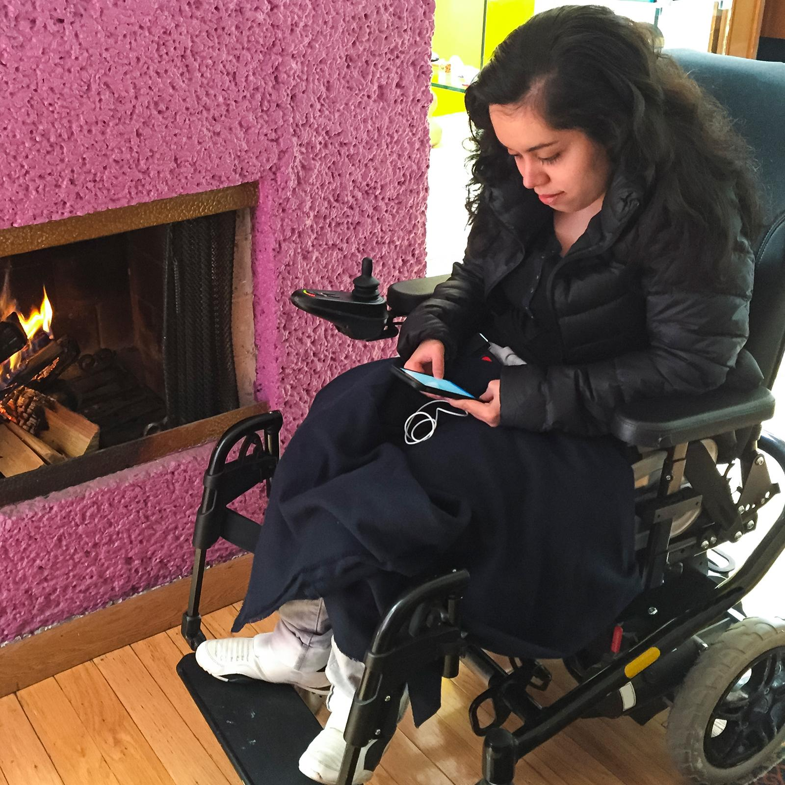 A young woman in a wheelchair looking at her mobile phone
